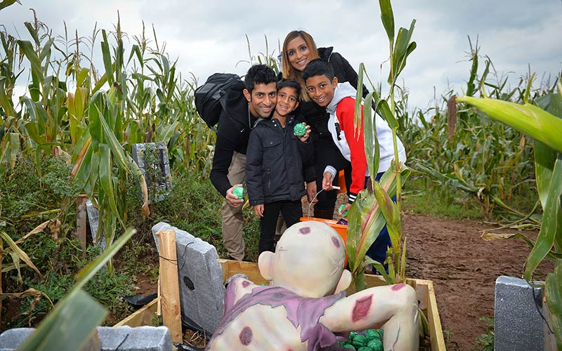 A family standing in a field of corn