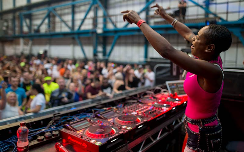 A woman DJ performing to a crowd of people